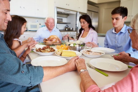 familia orando: Familia multi-generacional que dice rezo antes de comer comidas Foto de archivo