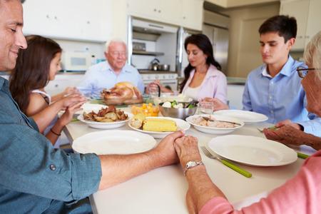 Multi-Generation Family Saying Prayer Before Eating Meal photo