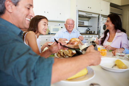 Multi-Generation Family Sitting Around Table Eating Meal Stock Photo
