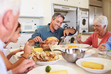 Multi-Generation Family Sitting Around Table Eating Meal Standard-Bild