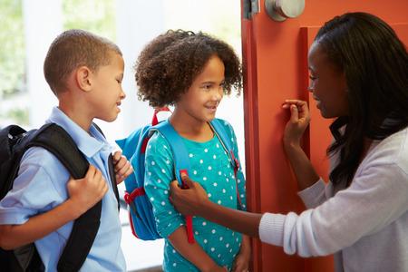 ni�os saliendo de la escuela: Madre Decir adi�s a los ni�os ya que van a la escuela Foto de archivo
