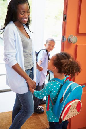 niños saliendo de la escuela: Madre Decir adiós a los niños ya que van a la escuela Foto de archivo