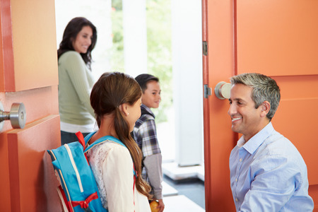 school aged: Father Saying Goodbye To Children As They Leave For School Stock Photo