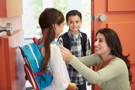 in the back: Mother Saying Goodbye To Children As They Leave For School Stock Photo