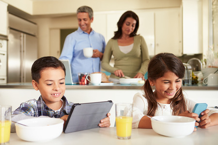 Hispanic Family Eating Breakfast Using Digital Devices photo