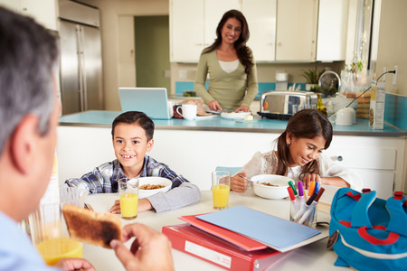 school aged: Hispanic Family Eating Breakfast At Home Before School
