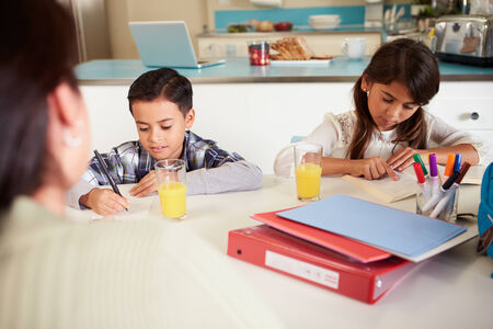 helping children: Mother Helping Children With Homework At Table