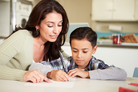 helping children: Hispanic Mother Helping Son With Homework At Table