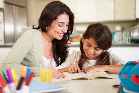 Mother Helping Daughter With Reading Homework At Table Banque d'images