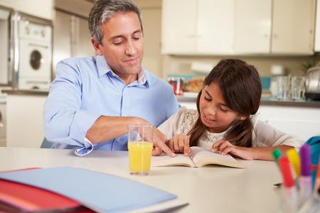 テーブルで宿題を読むと父を助ける娘