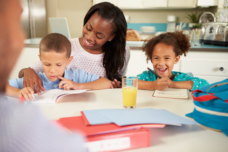 Mother Helping Children With Homework At Table photo