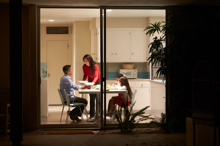 family indoors: Family Eating Evening Meal Viewed From Outside