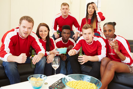 suspense: Group Of Sports Fans Watching Game On TV At Home Stock Photo