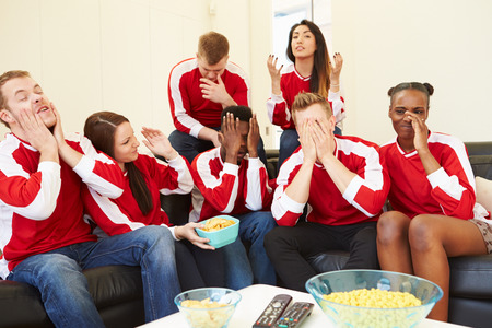 sports fans: Group Of Sports Fans Watching Game On TV At Home Stock Photo