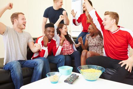 personas viendo television: Grupo de aficionados Deportes mirar del juego On TV en el país