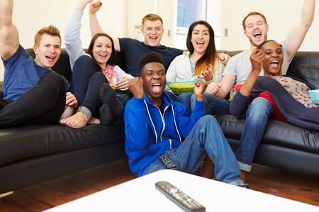 personas viendo television: Grupo de amigos que miran la televisión en el país junto
