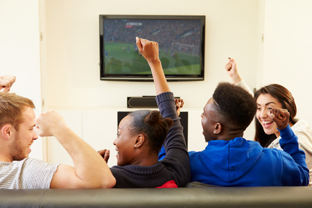 watching movie: Two Young Couples Watching Television At Home Together Stock Photo