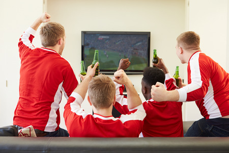 sports clothing: Group Of Sports Fans Watching Game On TV At Home Stock Photo