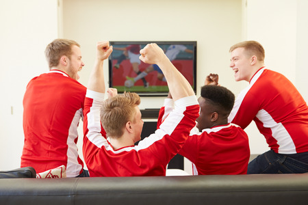match: Group Of Sports Fans Watching Game On TV At Home Stock Photo