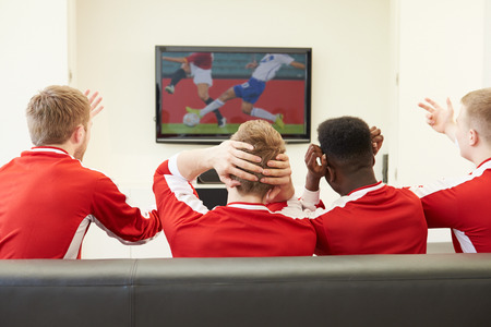 disappointed: Group Of Sports Fans Watching Game On TV At Home Stock Photo