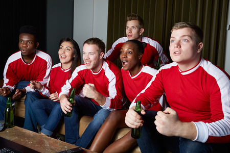 supporter: Group Of Sports Fans Watching Game On TV At Home Stock Photo