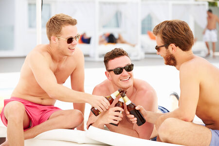 Three Young Male Friends On Holiday By Pool Together photo