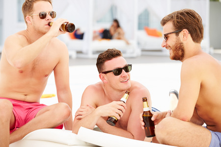 Three Young Male Friends On Holiday By Pool Together