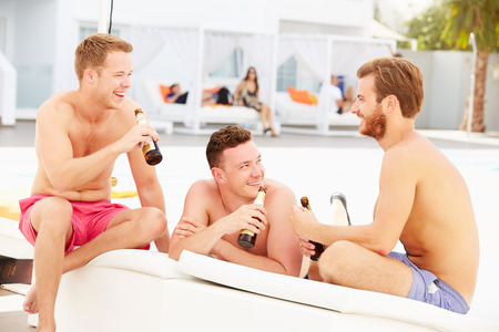 swimshorts: Three Young Male Friends On Holiday By Pool Together