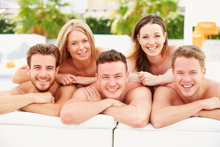 Group Of Young People On Holiday Relaxing By Swimming Pool photo