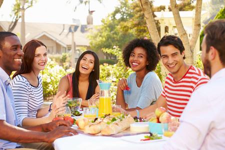 Gruppe Freunde, die Mahlzeit zu Outdoor Party In Back Yard Standard-Bild - 31066131