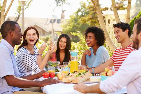 Groep Vrienden die van Maaltijd Op Outdoor Party in de achtertuin Stockfoto