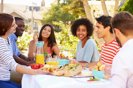 Group Of Friends Enjoying Meal At Outdoor Party In Back Yard