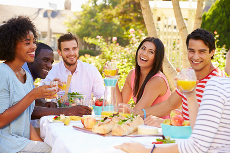 back yard: Group Of Friends Enjoying Meal At Outdoor Party In Back Yard