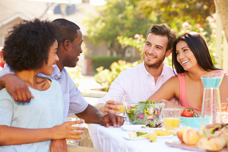 Group Of Friends Enjoying Meal At Outdoor Party In Back Yard photo