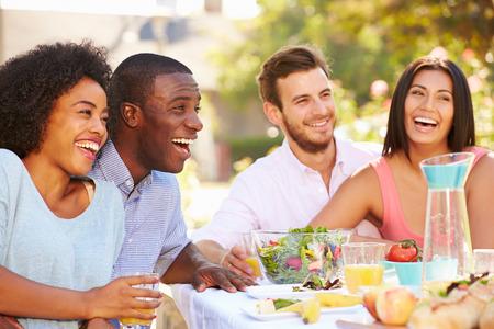 Skupina přátel si jídlo na venkovní strany na dvoře