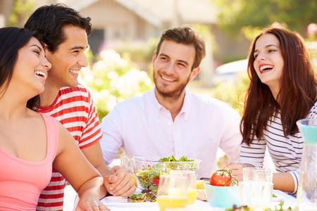 Groep Vrienden die van Maaltijd op outdoor feest in de achtertuin Stockfoto