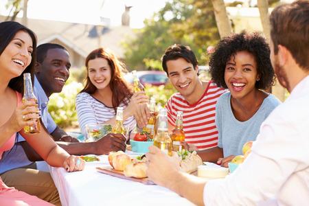 Gruppe Freunde, die Mahlzeit zu Outdoor Party In Back Yard