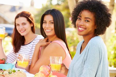 야외 파티에서 식사를 즐기는 세 여성 친구
