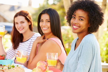 Three Female Friends Enjoying Meal At Outdoor Party Imagens