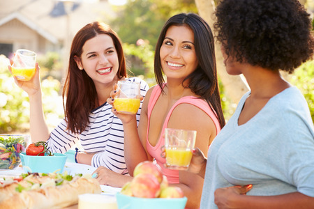 Three Female Friends Enjoying Meal At Outdoor Party photo