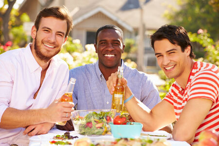 Three Male Friends Enjoying Meal At Outdoor Party photo