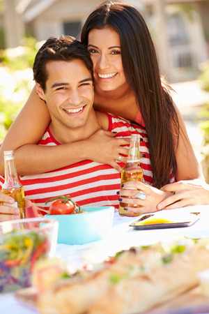 Romantic Couple Enjoying Outdoor Meal In Garden photo