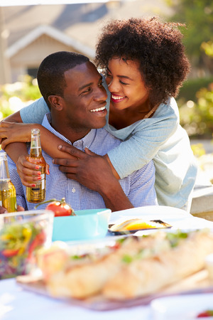 hombre tomando cerveza: Pares románticos que disfrutan de comidas al aire libre en el jardín