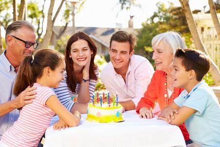 Multi-Generation Family Celebrating Birthday In Garden photo