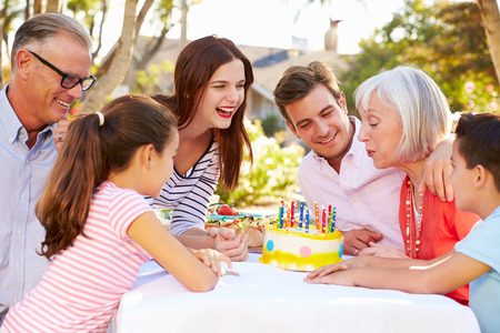 Multi-Generation Family Celebrating Birthday In Garden Stock Photo