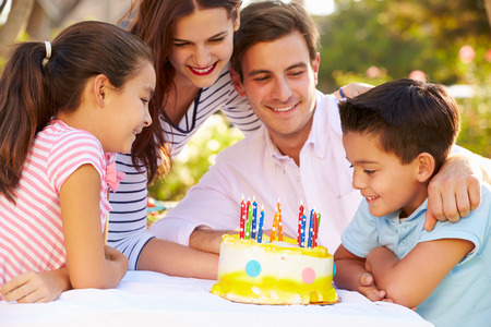 Family Celebrating Birthday Outdoors With Cake Stock Photo