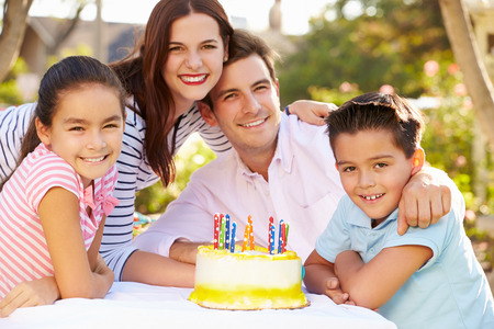 hispanic mother: Family Celebrating Birthday Outdoors With Cake Stock Photo
