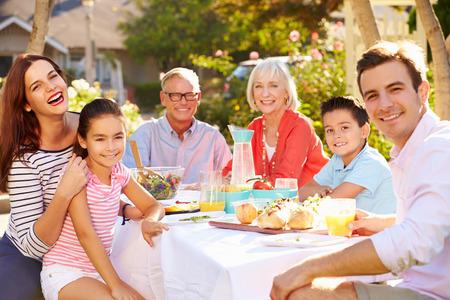 family picnic: Familia multi-generacional disfruta de la comida al aire libre en el jardín Foto de archivo
