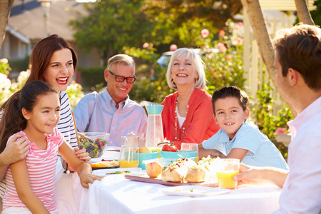 Multi-Generation Family Enjoying Outdoor Meal In Garden