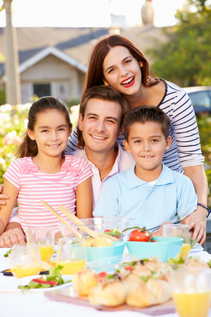 Familie genießen im Freien Mahlzeit im Garten Standard-Bild